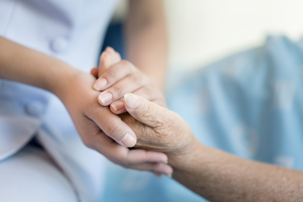 Nurse sitting on a hospital bed next to an older woman helping hands Premium Photo