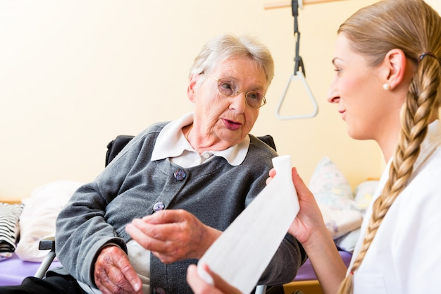 Nurse taking care of senior woman in retirement home Premium Photo