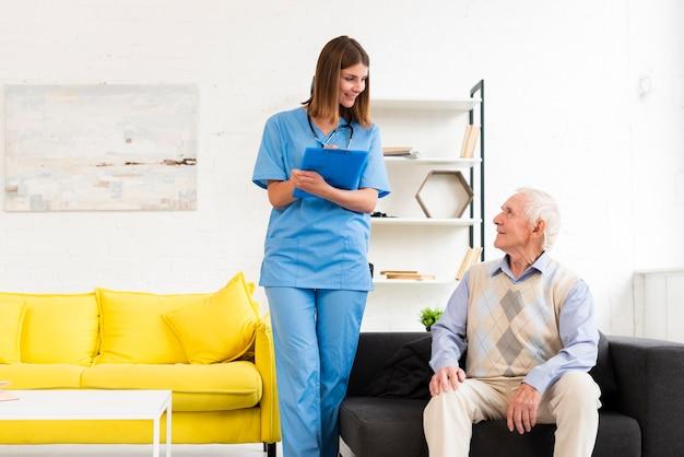 Nurse talking to old man sitting on black sofa Free Photo