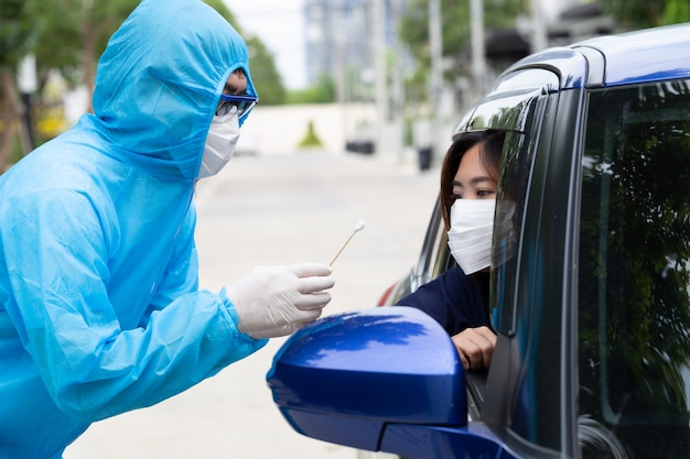 Nurse wearing ppe suit or medical workers in full protective gear takes sample from woman driver inside the car. drive-thru test for coronavirus covid-19 Premium Photo