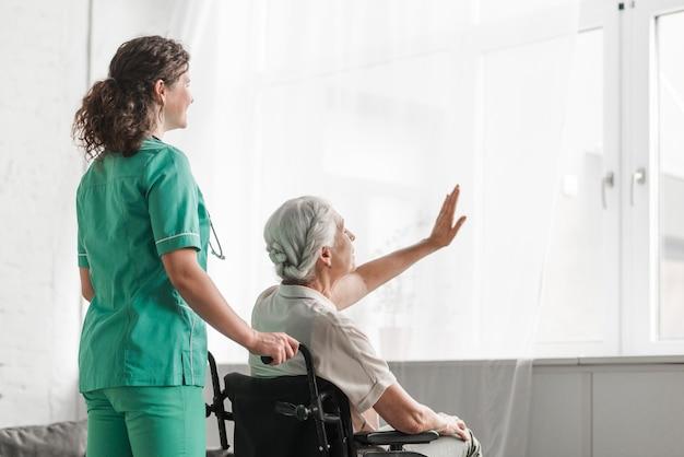 Nurse with senior woman sitting in wheelchair touching white curtain Free Photo