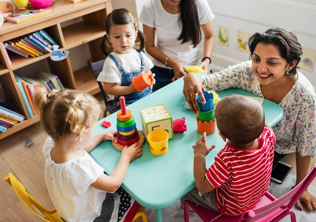 Nursery children playing with teacher in the classroom Premium Photo