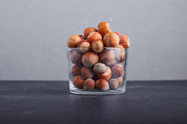 灰色の背景にガラスのカップのナッツの殻。 無料写真