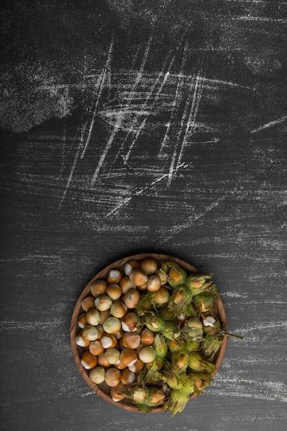 黒い背景に木製の大皿にナッツの殻 無料写真