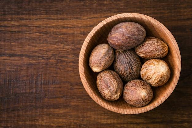Nutmeg closeup on wood Premium Photo