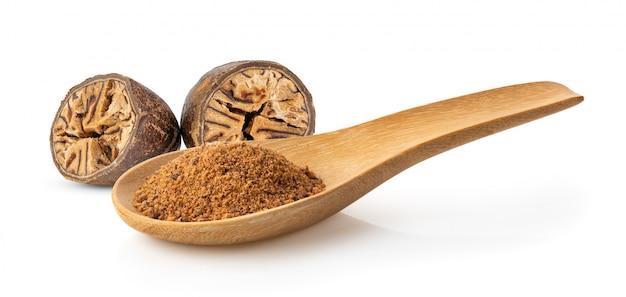 Nutmeg powder in wood spoon on white Premium Photo