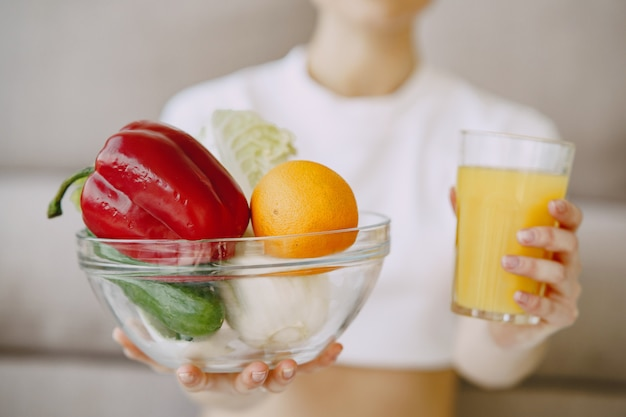 Nutritionist showing juice and vegetable bowl Free Photo