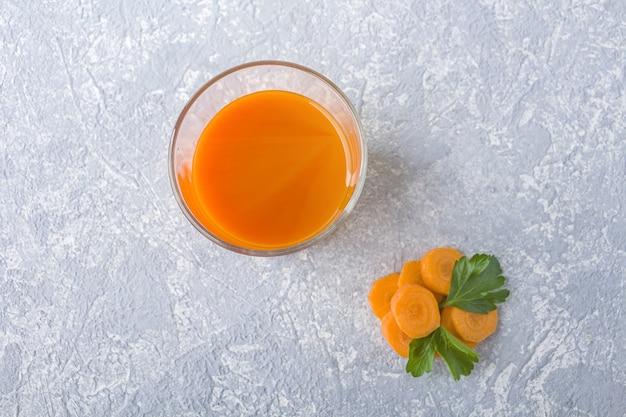 ガラスとパセリの葉で栄養価の高いデトックスキャロットジュース。アルカリダイエットのコンセプトです。オーガニックベジタリアンドリンク Premium写真