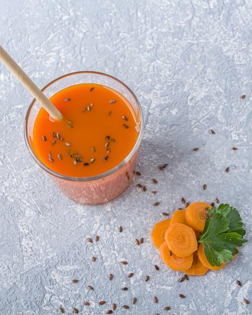 亜麻仁種子とパセリの葉とガラスの栄養価の高いデトックスキャロットジュース。アルカリダイエットのコンセプトです。オーガニックベジタリアンドリンク Premium写真