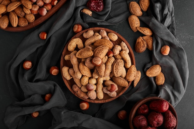 Nuts and almond shells in a wooden plate with dry fruits around. Free Photo