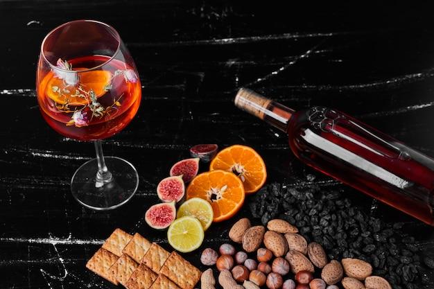 飲み物のガラスと黒の背景にナッツや果物。 無料写真