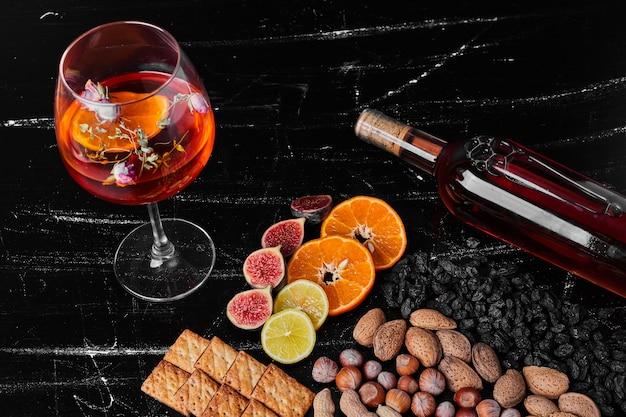 ワインと黒の背景にナッツや果物。 無料写真