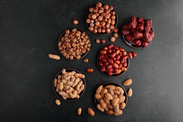 黒受け皿のナッツとスナック、上面図。 無料写真