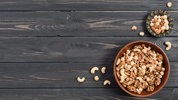 Nuts in the earthen and metallic bowls on black wooden desk Free Photo