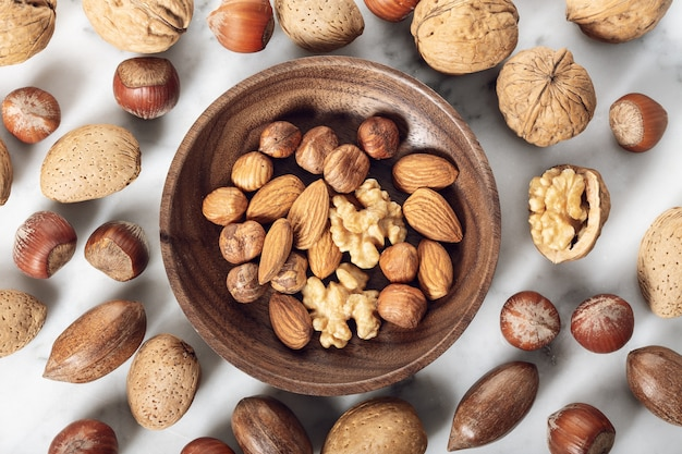 Орехи, смешанные в деревянной тарелке Premium Фотографии