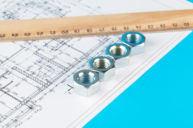 Nuts and parts of the construction are laid out in a dented drawing Premium Photo
