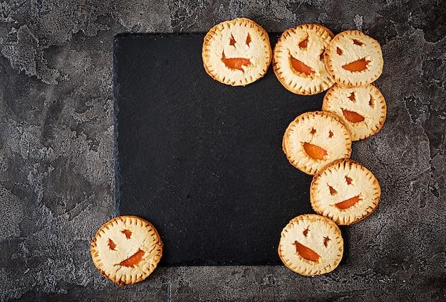 暗いテーブルの上のハロウィンジャック-o-ランタンカボチャの形の自家製クッキー。上面図。 無料写真