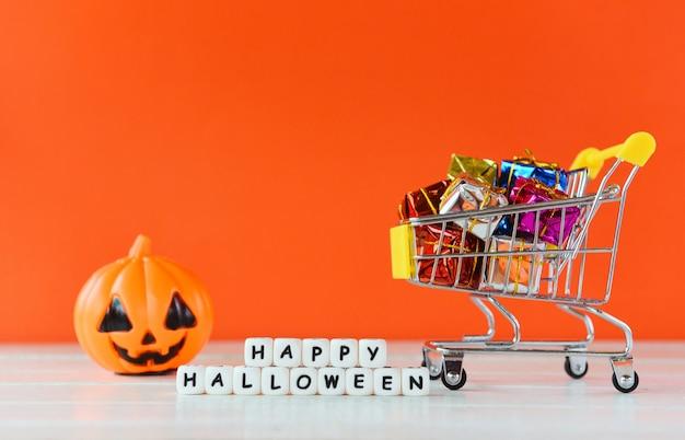ハロウィーンショッピングホリデーコンセプト-単語ブロック幸せなハロウィーンの装飾とショッピングカートのギフトボックスとカボチャジャックoランタン Premium写真