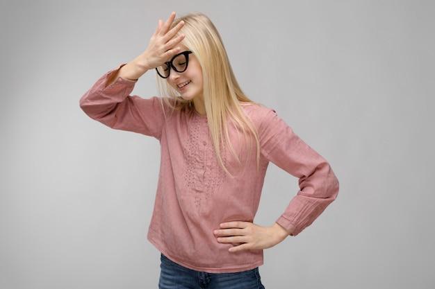 ピンクのブラウスoのメガネで魅力的な甘い笑顔かわいい金髪のティーンエイジャーの女の子の肖像画 Premium写真