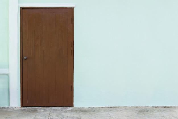 Oak wood door in white concrete wall background Premium Photo