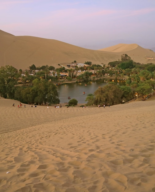 The oasis town of huacachina as seen from the sand dune at sunset, ica region, peru Premium Photo