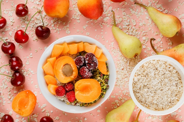 Oat flakes in bowls with pear, orange, cherry, apricot, berries Free Photo
