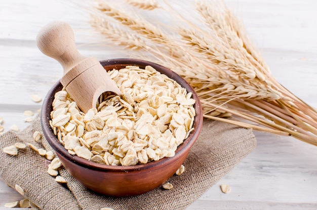 Oat flakes  in ceramic bowl and wooden spoon and spikelets Premium Photo
