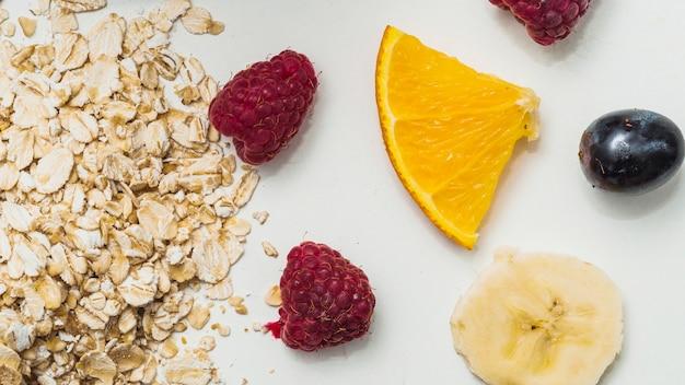 Oat flakes; raspberry; grapes; slice of lemon and banana on white background Free Photo