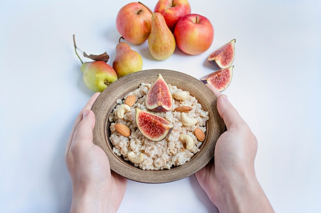 Oatmeal in a bowl with fresh figs, almonds and cashews oatmeal with fruits. men's hands hold a bowl of porridge. white . Premium Photo