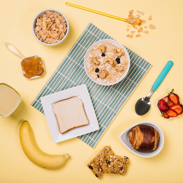 Oatmeal in bowl with toast and fruits on table Free Photo