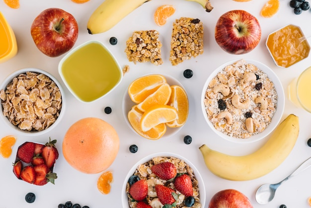 Oatmeal in bowls with fruits and berries on white table Free Photo