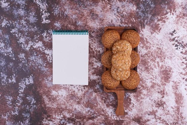 Овсяное печенье на деревянном блюде с блокнотом в сторону. Бесплатные Фотографии