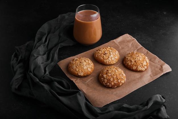 ホットチョコレートのガラスと黒い表面のオートミールクッキー。 無料写真