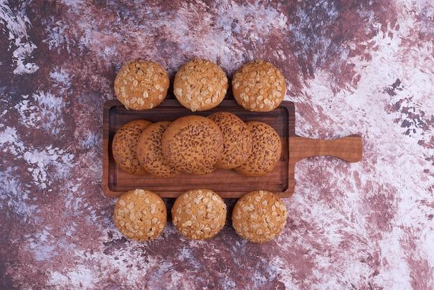 Овсяное печенье с черным тмином на деревянном блюде в центре. Бесплатные Фотографии