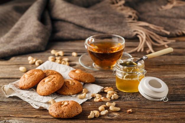 ナッツとオートミールクッキー、茶色の木製のテーブルにナプキンに蜂蜜と瓶。食品、休日、料理、ベーキングテーブル。家庭と健康的な食事のコンセプトです。 Premium写真