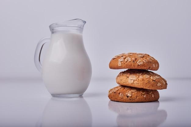オートミールクラッカーは灰色のミルクの瓶を添えてください。 無料写真