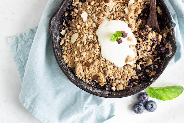 Oatmeal crumble in cast iron pan with fresh blueberry and natural yogurt. Premium Photo