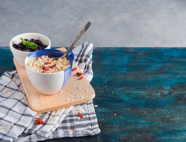 Oatmeal in cup with berries in bowl on wooden board Free Photo