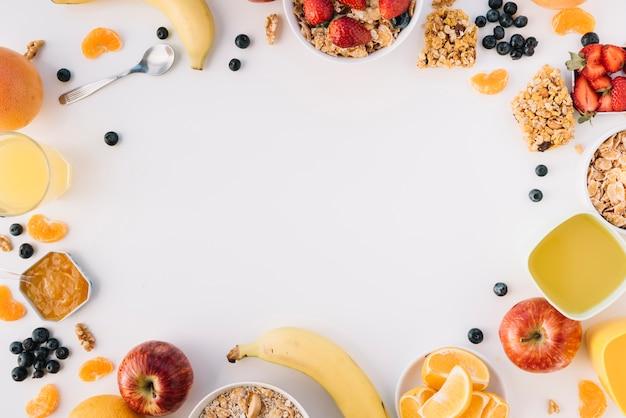 Овсянка в мисках с фруктами и ягодами на светлом столе Premium Фотографии