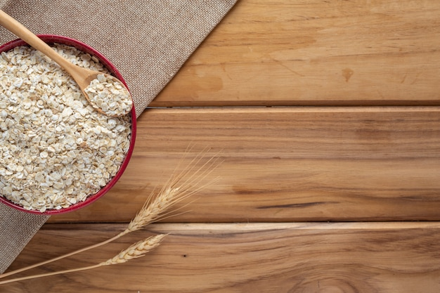 Oatmeal is placed on a brown wood . Free Photo
