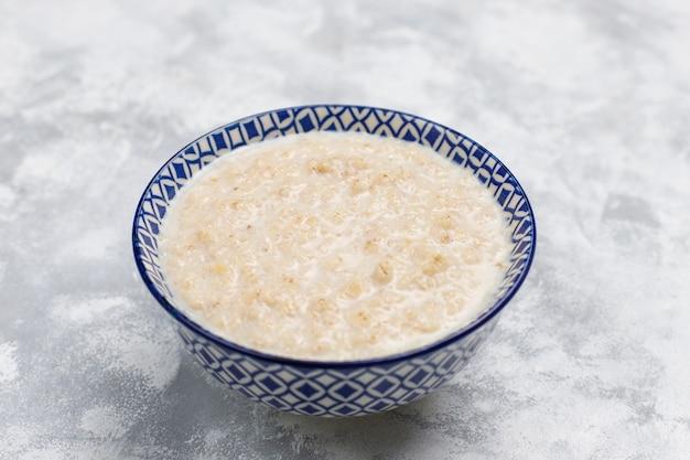 Oatmeal porridge in a bowl on concrete ,top view Free Photo