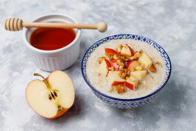 Oatmeal porridge in a bowl with honey and red apple slices,top view Free Photo