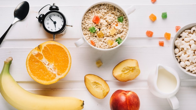 Oatmeal porridge, fruits, cereals and milk with alarm clock on white table Free Photo