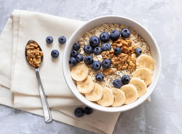オートミール。健康的な朝食やランチにバナナ、ブルーベリー、クルミの粥。 Premium写真