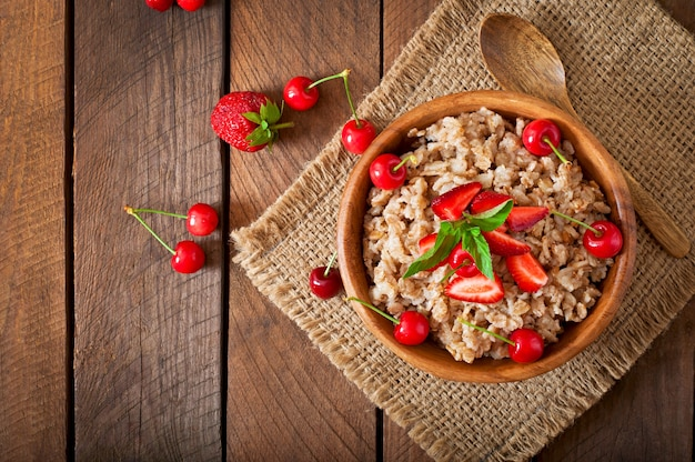 Oatmeal porridge with berries in a white bowl Free Photo