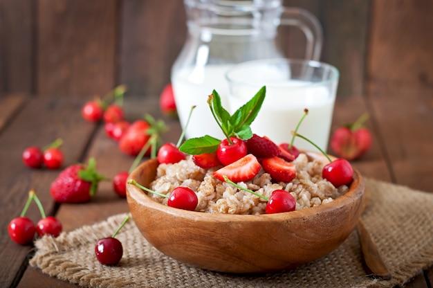 Oatmeal porridge with berries in a white bowl Free Photo