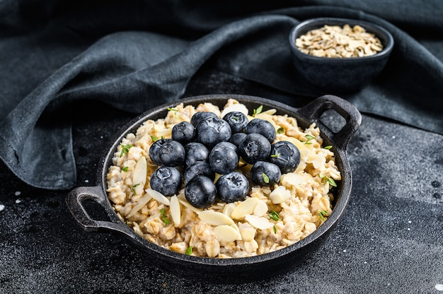 Oatmeal porridge with blueberries and almonds. black background. top view. Premium Photo