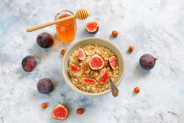 Oatmeal porridge with red figs and walnuts, honey in a bowl Free Photo