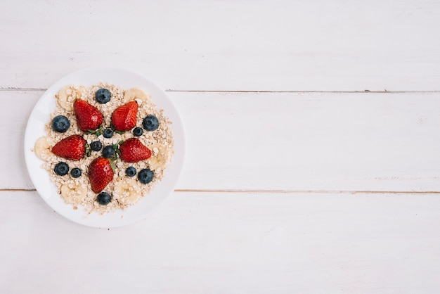 Oatmeal with different berries in bowl on wooden table Free Photo