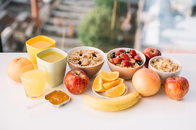 Oatmeal with fruits and juices on table Free Photo